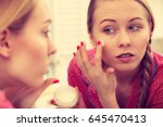 young blonde woman applying... | Shutterstock . vector #645470413