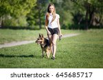 Stock photo teenage girl in white shirt with her german shepherd dog walking in the park 645685717