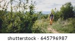Stock photo man with a dog walking along a hiking trail on the mountain 645796987