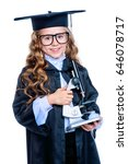 Small photo of Portrait of a cute nine year old girl in an academic gown and hat holding a microscope. Educational concept. Isolated over white.