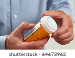 Close up of patient pouring out RX pills into hand selective focus - stock photo