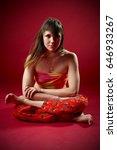 Small photo of Beautiful sporty fit yogi woman practices yoga asana Agni Stambhasana - Fire Log pose on the red background. studio shot.