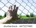 Small photo of Refugee hand on fence. Refugee concept.Dark tone. Vintage.The control strip at the border