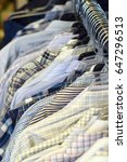Small photo of Clothing racks of mens shirts at a stylish consignment boutique