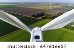 Small photo of Aerial photo close up of wind turbine showing dirty blades pointing upwards mill located on grassland also showing more aerofoil powered windmills providing sustainable energy