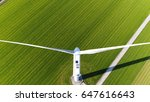 Small photo of Aerial photo of wind turbine blades sideways mill located on grassland top down view looking down on large white windmill aerofoil powered windmills providing sustainable energy