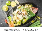 Small photo of Gish. seafood. Asian and Eastern cuisine. Red tilapia roasted on a grill in leaves of leeks with slices of lime, herbs and spices. In the frying pan, grill. Top view copy space, with fork and knife