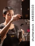 Small photo of A barista girl is cooking a cup of ice Americano coffee.
