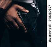Small photo of Unrecognizable armed black criminal man closeup studio shoot. Gangster guy with gun in hand on dark background. Outlaw, ghetto, murderer, robbery concept