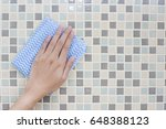 cleaning tile wall by woman hand | Shutterstock . vector #648388123