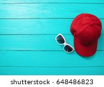 red cap and sunglasses on blue... | Shutterstock . vector #648486823