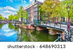Stock photo bridge over channel in amsterdam netherlands houses river amstel landmark old european city spring 648690313