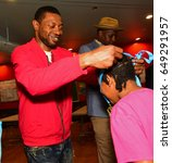 Small photo of NEW YORK CITY - MAY 26 2017: Brooklyn Police Athletic League & King's County DA's office sponsored an afterschool chess program for Bed-Stuy elementary students. Erick Barkley confers medals