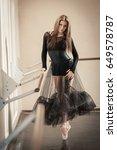 Small photo of Beautiful female contemporary ballet dancer in black wear posing on a tiptoe at ballet barre in a dance studio.