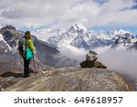 Small photo of Young Woman hiker with backpack and hiking poles is standing and looking on Ama Dablam mountain. Cloudy sky. Himalaya, Nepal.