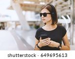 Small photo of European hipster girl in the earphones standing near the city rail holding smartphone in hands and listening to music while waiting for the train. Urban life concept. Copy space for your text.