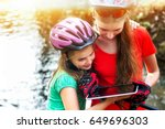 Small photo of Bikes cycling girl. Children rides bicycle. Bicyclist girl watch on tablet computer. Kids looking for way. Dependence of adolescents on gadgets. Sports orienteering.