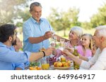 extended family eating outdoors  | Shutterstock . vector #649964917