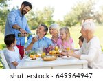 extended family eating outdoors | Shutterstock . vector #649964947