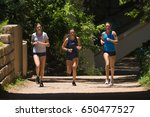 Small photo of AUSTIN, TEXAS - MAY 25 2017: three young women running abreast on a shaded trail