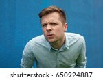 Small photo of I don't know. Portrait of doubtful caucasian male wearing casual blue shirt, looking with indecisive expression on his face, showing doubt and hesitation. Body language