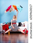 Small photo of Cleaning in the closet, packing for travel, fashion, happiness concept. Woman sitting on sofa throwing up lot of clothes. Clothing flying all over the place