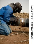 Welder worker fixing industrial construction oil and gas plumbing pipeline - stock photo