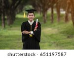 Small photo of Graduated admirer admired graduation At the lush greenery.