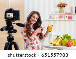 woman holding a glass of orange ... | Shutterstock . vector #651557983