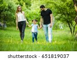 happy young family walking in... | Shutterstock . vector #651819037