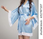 Small photo of Girl in blue silk robe, on gray background
