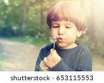 child little boy blowing on a... | Shutterstock . vector #653115553