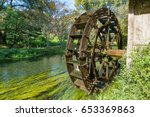 Small photo of Water mill wheel on river on sunny day. Sustainable energy and water power traditional machinery
