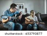 father teaching his son to play ... | Shutterstock . vector #653793877