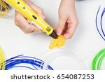 kid hand holding yellow 3d... | Shutterstock . vector #654087253