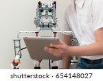 a boy and a robot assembled... | Shutterstock . vector #654148027