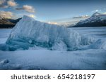 Small photo of A large chunk of ice heaved out of the frozen lake bed creating a mountain shape as the ones in the background.
