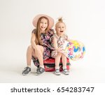 happy sisters are sitting on a... | Shutterstock . vector #654283747