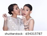 Two beautiful lovely sisters sharing a secret together by whispering man things, whtie lace dress over studio lighting white background isolated copy space