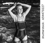 Small photo of Fun weekend alfresco. relaxed healthy woman in blue swimwear standing in the swimming pool