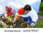 Boy Watering Plants With...