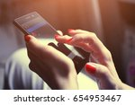 female hands hold a mobile phone | Shutterstock . vector #654953467