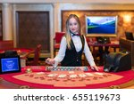 Small photo of Cute lady casino dealer at Black Jack table.