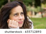 Small photo of Beautiful mature woman portrait in the park resting chin on hand with her mind somewhere else. Middle aged attractive lady with optimistic expression, positive, dreamer, thoughtful concept