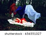 Small photo of A girl in the similitude of a fairy sleeping in a forest.