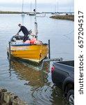 Small photo of AMBLE, NORTHUMBERLAND, ENGLAND, UK. MAY 28. 2017. Fishing Boat (Coble) loading onto trailer from water. May 28.2017, Amble, Northumberland, England, UK.