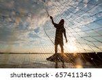A Fisherman Cast A Net At Lake...