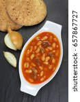 Small photo of Traditional Turkish cuisine. Kuru Fasulye . Haricot Beans with onion and rustic bread on black stone background.