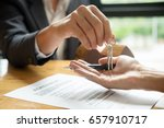 Small photo of real estate agent holding house key to his client after signing contract agreement in office,concept for real estate, moving home or renting property