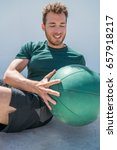 Small photo of Gym workout with medicine ball exercise man doing russian twist exercises. Athlete working out doing exercises training oblique abs muscles on fitness centre floor.
